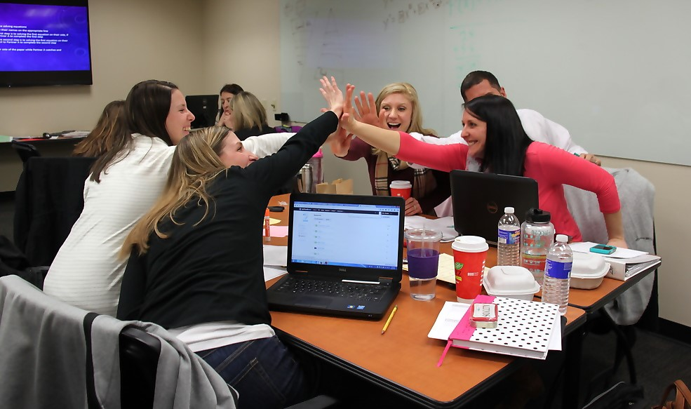 Math workshop participants collectively high-fiving