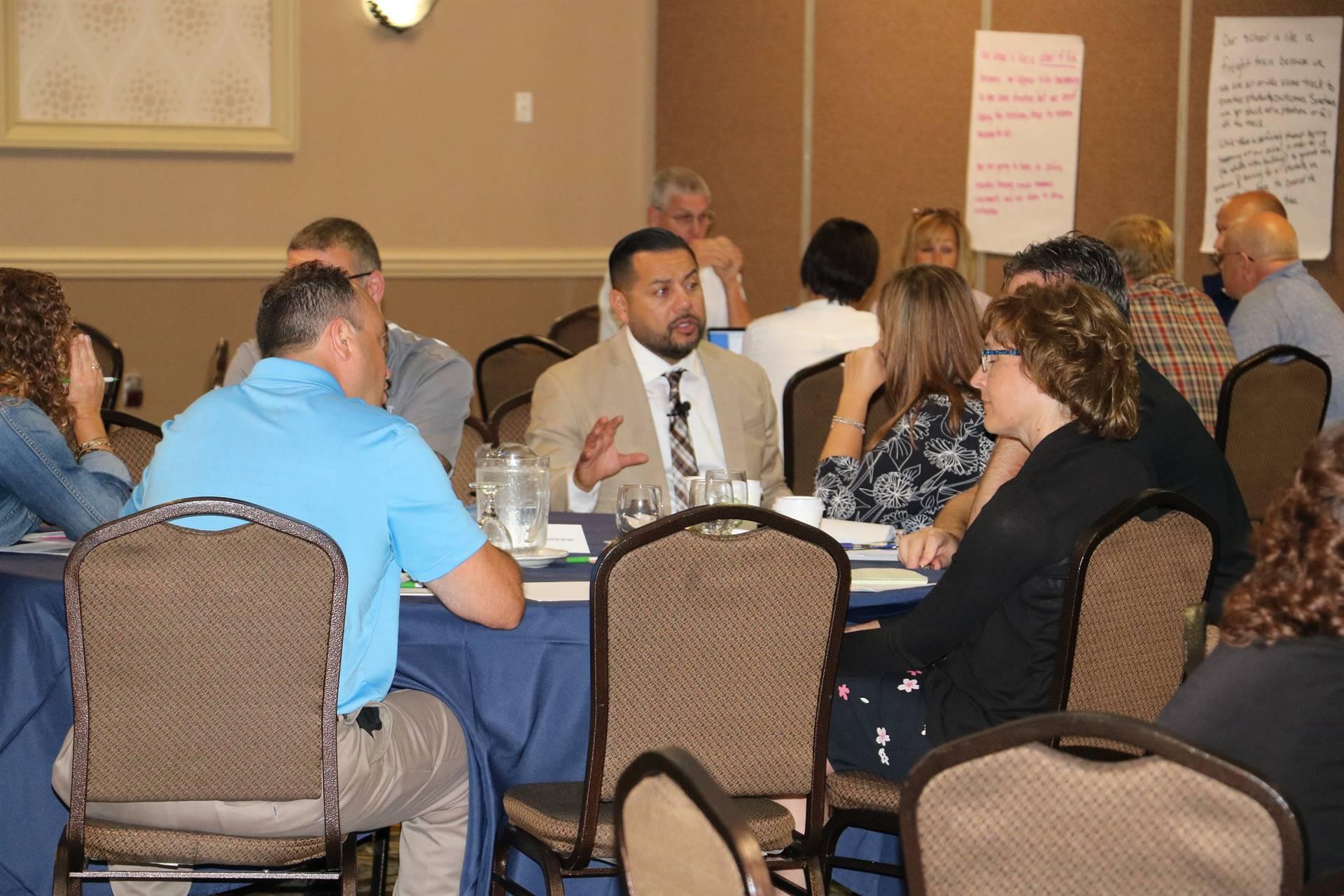 Principals' Academy Participants having discussion with presenter, Dr. Luis Cruz